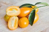 foto of kumquat  - handful of fresh kumquat over rough wood - JPG