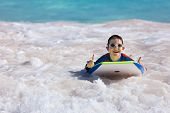 foto of boogie board  - Little boy on vacation having fun swimming on boogie board - JPG