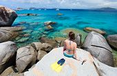 Young woman with snorkeling equipment enjoying aerial view of a tropical beach sitting on granite bo
