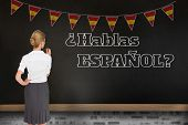 Thinking businesswoman against blackboard on wall, Do you speak Spanish?