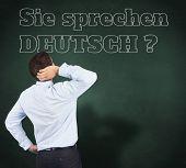 Thinking businessman scratching head against green chalkboard, Do you speak German?