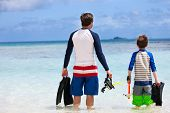Back view of father and son with snorkeling equipment fins and mask at tropical beach