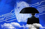Mature businessman holding an umbrella against fingerprint on digital blue background