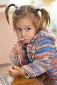 Cute little girl drinking juice