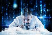 Mature businessman examining with magnifying glass against lines of blue blurred letters falling