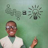 Cute pupil pointing against idea and innovation graphic