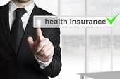 pic of insurance-policy  - businessman in black suit pushing button health insurance - JPG