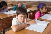 stock photo of pupils  - Bored pupil sitting at his desk at the elementary school - JPG