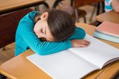 Sleeping pupil sitting at desk at the elementary school