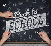 Multiple hands writing with chalk against blackboard on wall