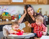 stock photo of babysitter  - Stressed out mother in kitchen with her babies - JPG