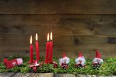 Four Red Burning Christmas Candles On Wooden Background With Green Moss.