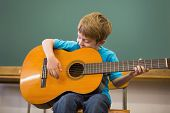 Cute pupil playing guitar in classroom at the elementary school