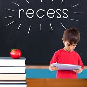 The word recess and cute boy using tablet against red apple on pile of books in classroom