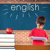 The word english and cute boy using tablet against red apple on pile of books in classroom