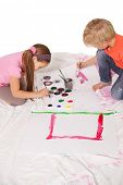 Happy little children painting on the floor on white background