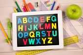 Composite image of digital tablet on students desk showing alphabet