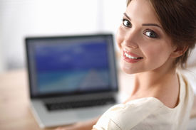 pic of secretary  - Portrait of beautiful young business woman working on a laptop at office - JPG