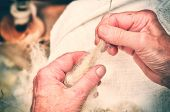 pic of thread-making  - Hands of an old woman making traditional wool spinning - JPG