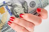 girl with red manicure gives money. denominations hundred dollars