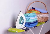 Ironing board with laundry on light background