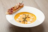 Pumpkin Cream Soup Purée With Bread Slice, Bacon And Seeds