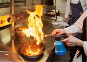 Chef is burning aromatic herbs to smoke a dish, commercial kitchen