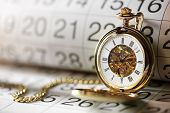 Pocket watch against a calendar concept for planning or scheduling