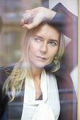 Blond Woman Looking Out Of Window