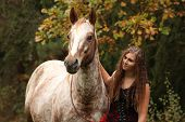stock photo of appaloosa  - Amazing girl standing next to the appaloosa horse in autumn - JPG