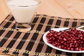 stock photo of wallow  - red grains of a pomegranate and milk on the wooden background - JPG
