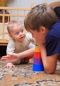 stock photo of bassinet  - two brothers play at home on the carpet - JPG