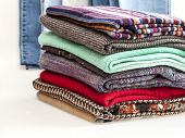 Pile of woolen jumpers of various colors and textures