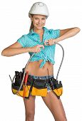 Pretty girl in helmet, shorts, shirt and tool belt with tools connects two flexible hose for plumbin