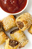 Sausage rolls with tomato sauce or ketchup.  Overhead view.