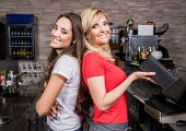 Two smiling waitress in a coffee shop