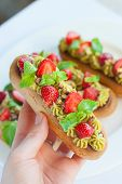 stock photo of eclairs  - French eclairs with whipped cream and topped with strawberries mint and pistachios on a white plate - JPG