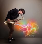 picture of fumes  - Attractive young musician playing on saxophone with colorful abstract fume comming out - JPG