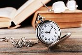 Silver pocket clock and book on wooden table
