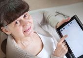 Pension age good looking woman looking internet in tablet device.