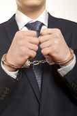 Worried caucasian middle aged businessman in handcuffs