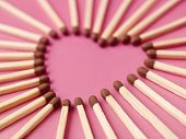 Matches formed as a heart on pink background