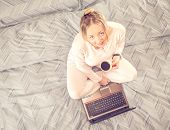 stock photo of bed breakfast  - Young woman siiting on bed with a cup of coffee and computer  - JPG
