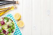 Fresh healthy salad and condiments over white wooden table. View from above with copy space