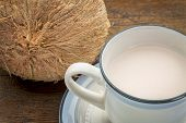 a cup of coconut milk with a coconut against wood background