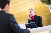 Hotel receptionist telephoning with guest for reservation or information