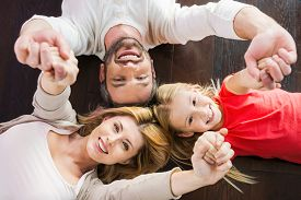 stock photo of bonding  - Top view of happy family of three bonding to each other and smiling while lying on the hardwood floor - JPG