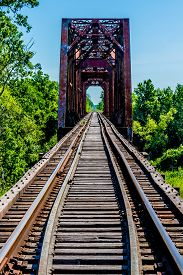image of trestle bridge  - Vanishing Point View of an Old Railroad Trestle with an Old Iconic Iron Truss Bridge Over the Brazos River - JPG