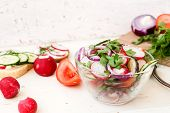 stock photo of chinese parsley  - Spring salad with radishes cucumber Chinese cabbage and red onion closeup  on a white wooden background - JPG