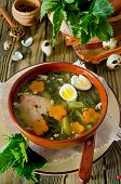 stock photo of nettle  - Nettle soup with eggs and carrot in the bowl on the wooden table - JPG